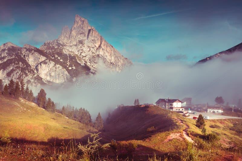 Mt. Sass de Stria in the morning mist. Summer scene in the Falzarego pass. Foggy sunrise in Dolomite Alps, Italy, Europe. Retro style tonned stock photo