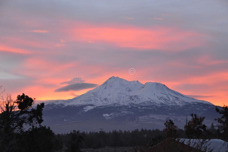 Mt Shasta with odd clouds at sunrise royalty free stock photo