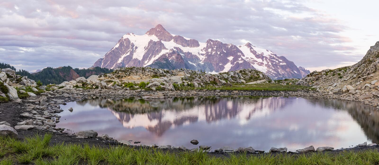 Mt. Shuksan Tarn Panorama. Mt. Shuksan and colorful sunset clouds reflected in a tarn on Artist Ridge in Mt. Baker-Snoqualmie National Forest, Washington royalty free stock photography
