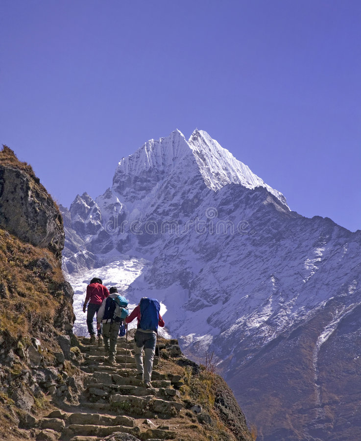 Mt. Thamserku and trekkers stock photography