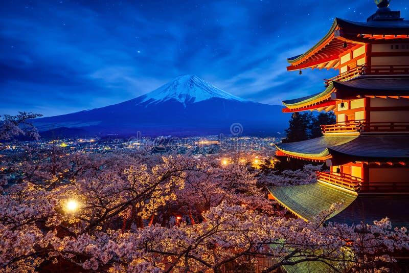 MT van de nachthemel Fuji en tempel rode pagode in Fujiyoshida met kersenbloesem royalty-vrije stock fotografie