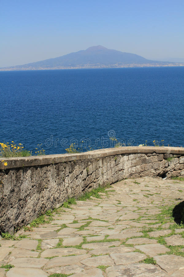 Mt. Vesuvius from the Sorrento waterfront. Mt. Vesuvius and Naples across the Mediterranean Sea from Sorrento. This winding stone stairway and wall are part of royalty free stock photography