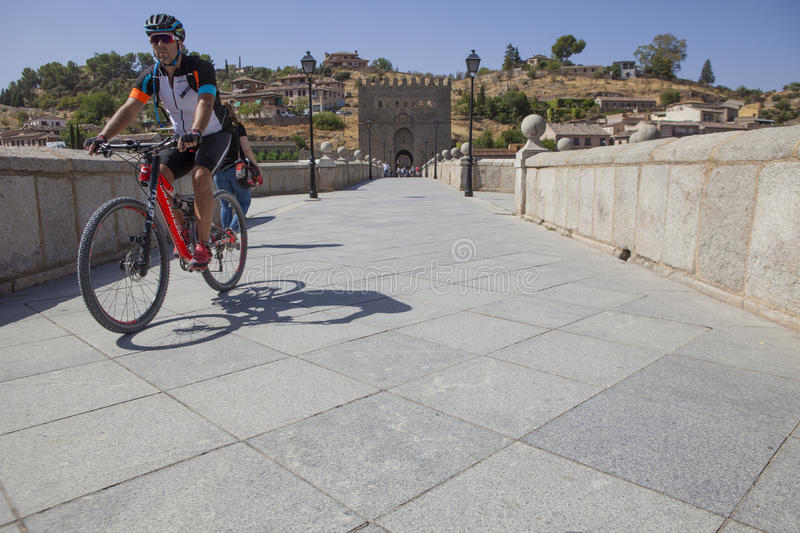 MTB biker crossing Saint Martin medieval bridge, Toledo, Spain royalty free stock photos