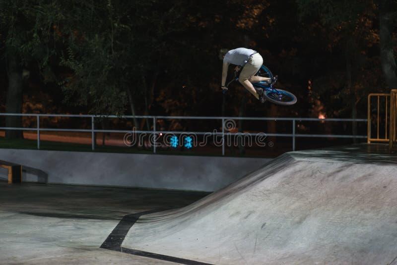 MTB-cykelryttaren gör olika trick, medan rida i skatepark Extrema sportar, ryttare gör tabletoptrick på natten royaltyfria bilder