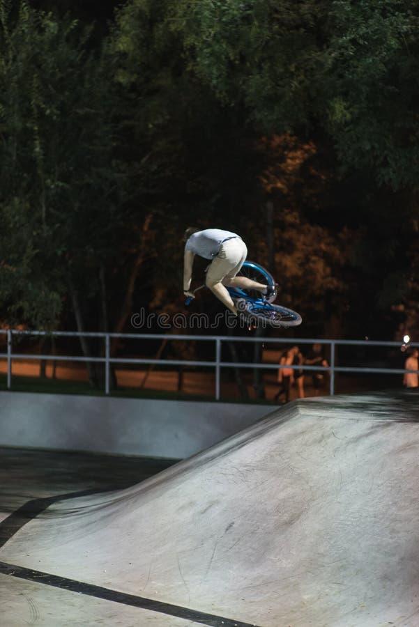 MTB-cykelryttaren gör olika trick, medan rida i skatepark Extrema sportar, ryttare gör tabletoptrick på natten fotografering för bildbyråer