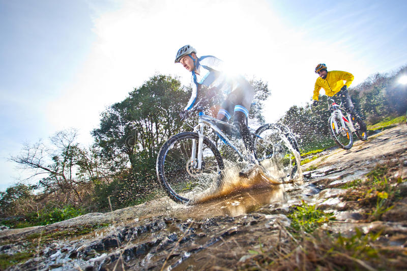Mtb extreme splash. Mtb extreme biking downhill on hard tail trough water splashing royalty free stock photo