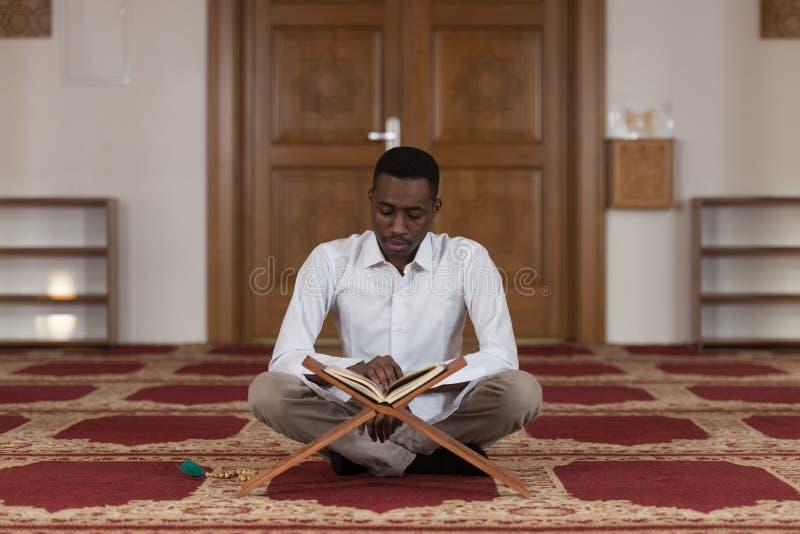 Muçulmanos africanos novos Guy Reading The Koran imagem de stock royalty free