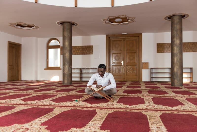 Muçulmanos africanos novos Guy Reading The Koran fotos de stock