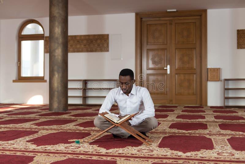 Muçulmanos africanos novos Guy Reading The Koran imagens de stock royalty free