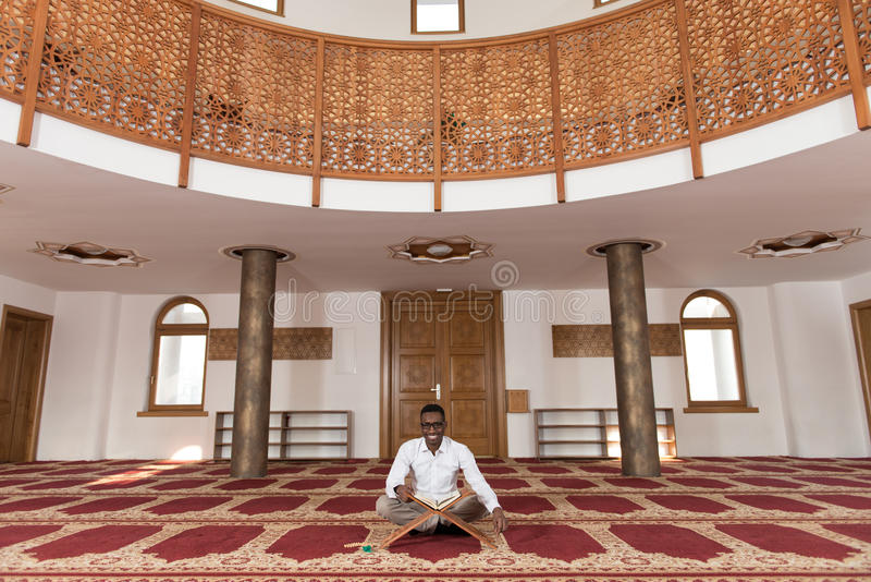 Muçulmanos africanos novos Guy Reading The Koran foto de stock royalty free