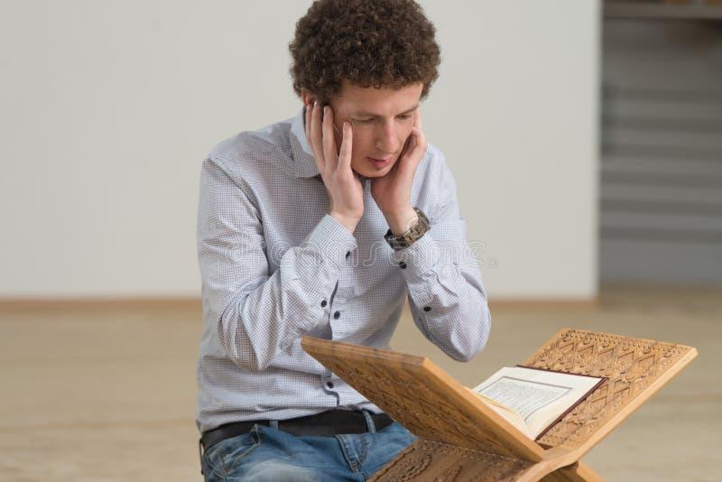 Muçulmanos brancos Guy Reading The Koran foto de stock