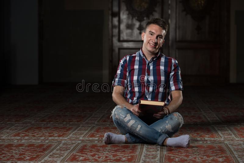 Muçulmanos novos Guy Reading The Koran imagem de stock royalty free