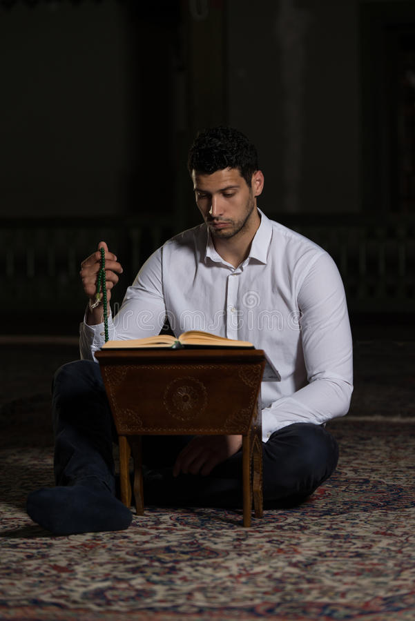 Muçulmanos novos Guy Reading The Koran imagens de stock royalty free