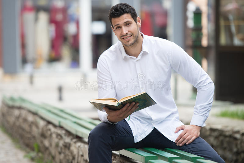 Muçulmanos novos Guy Reading The Koran imagem de stock