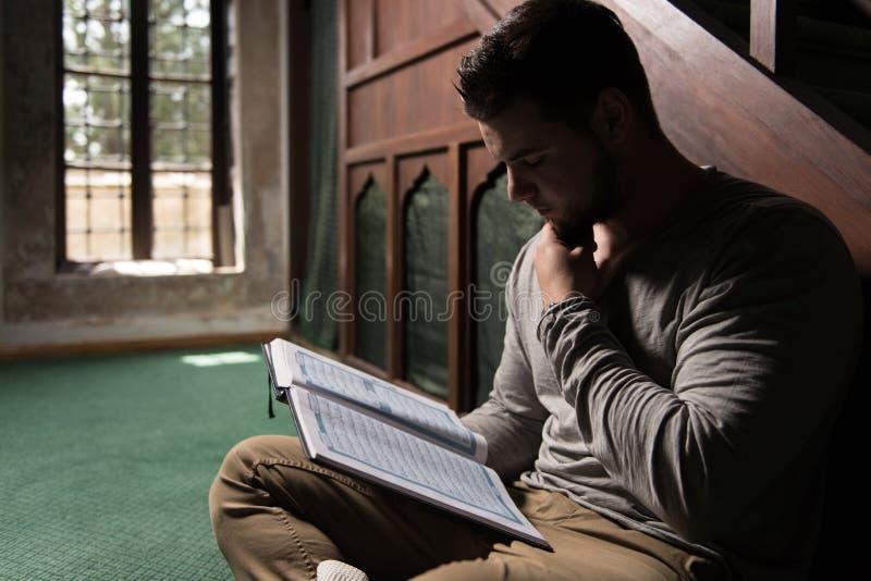 Muçulmanos novos Guy Reading The Koran imagem de stock royalty free