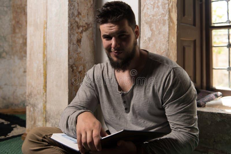 Muçulmanos novos Guy Reading The Koran fotografia de stock royalty free