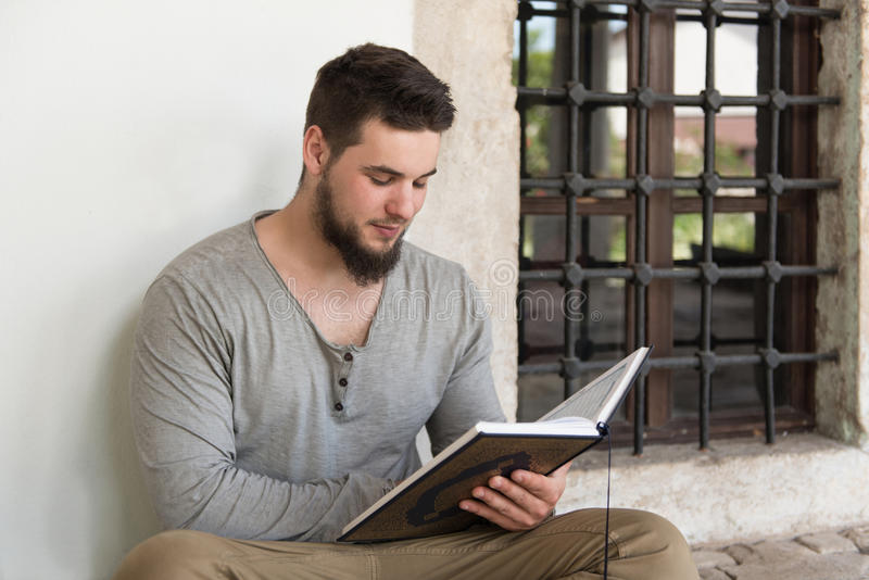 Muçulmanos novos Guy Reading The Koran foto de stock
