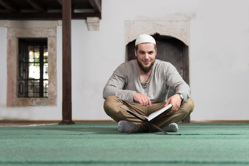 Muçulmanos novos Guy Reading The Koran foto de stock royalty free