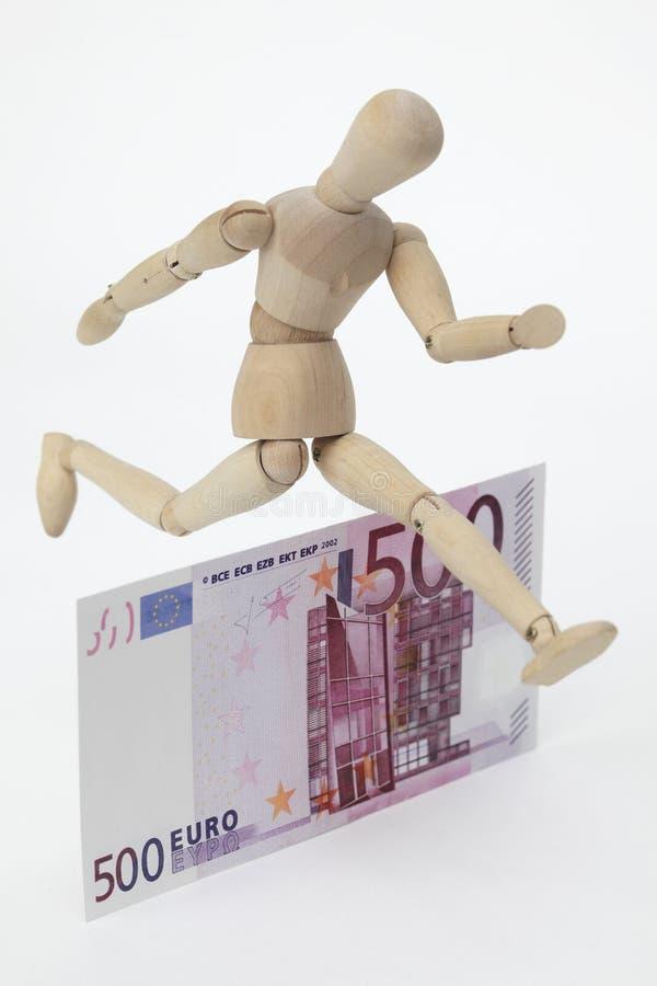 Muñeca articulada que salta sobre un 500-Euro-Banknote imagen de archivo libre de regalías