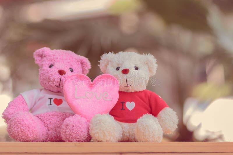 muñeca de dos osos que se sienta junto, día del ` s de la tarjeta del día de San Valentín y concepto del amor fotografía de archivo
