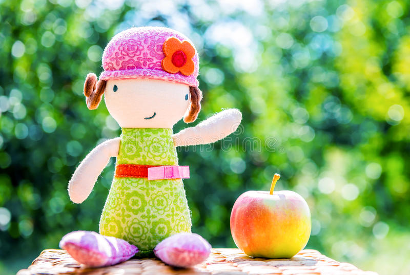 Muñeca de la felpa que se sienta cerca de manzana fotografía de archivo