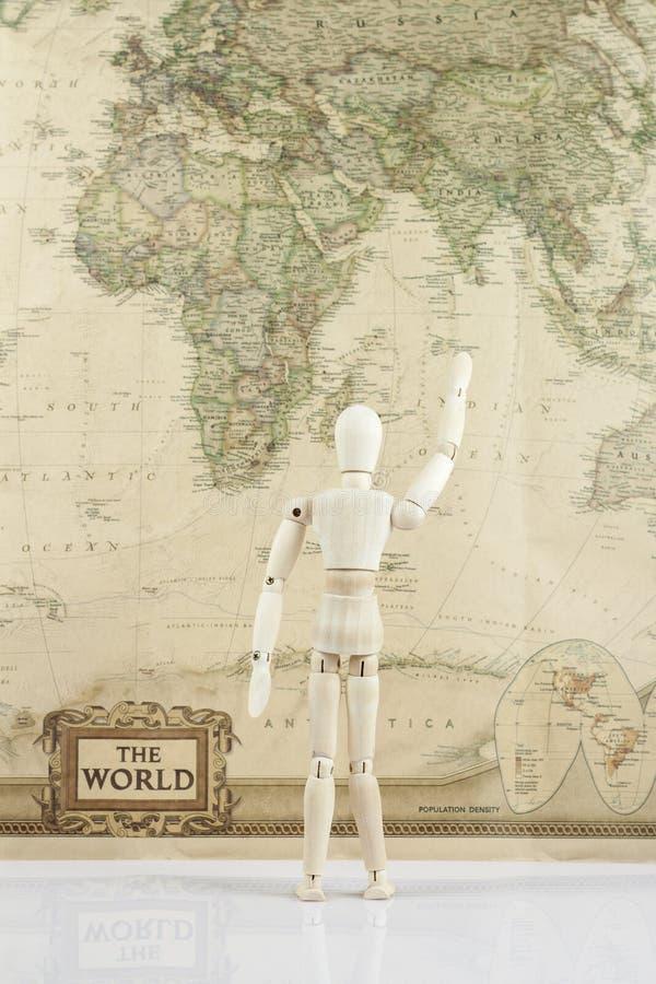 Muñeca de madera con la mano para arriba que mira en mapa del mundo imágenes de archivo libres de regalías