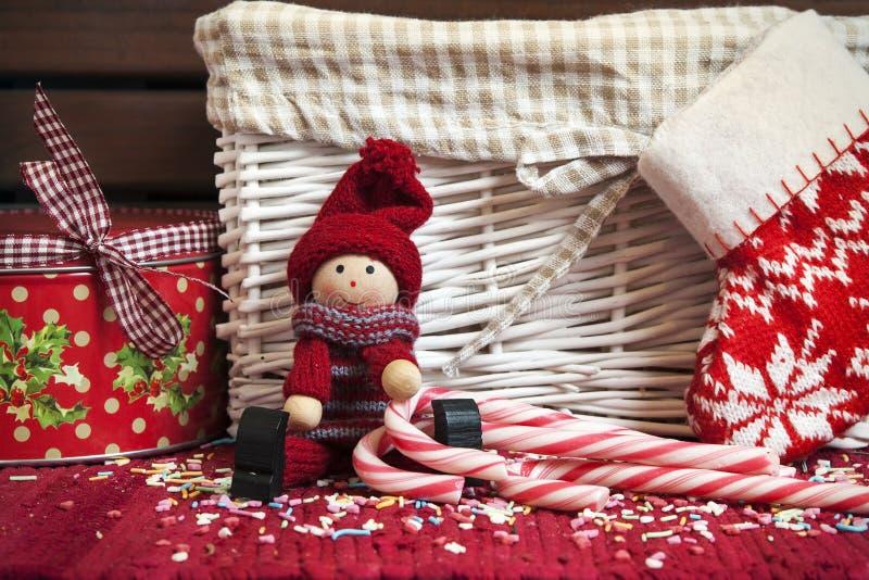 Muñeca de madera decorativa de la Navidad con el calcetín de la caja y de Navidad de regalo. foto de archivo