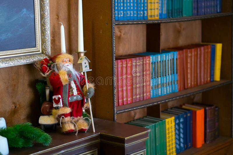 Muñeca de Papá Noel en la repisa en la biblioteca El libro es el foco selectivo del fondo fotos de archivo libres de regalías