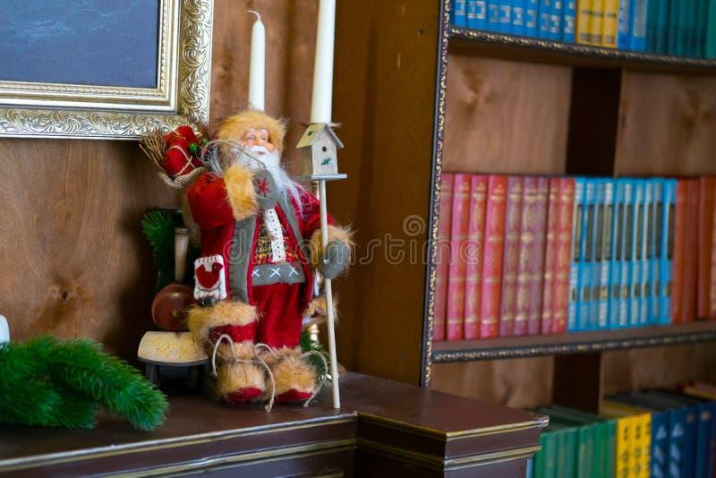 Muñeca de Papá Noel en la tabla con las velas en la biblioteca El libro es el foco selectivo del fondo imagenes de archivo