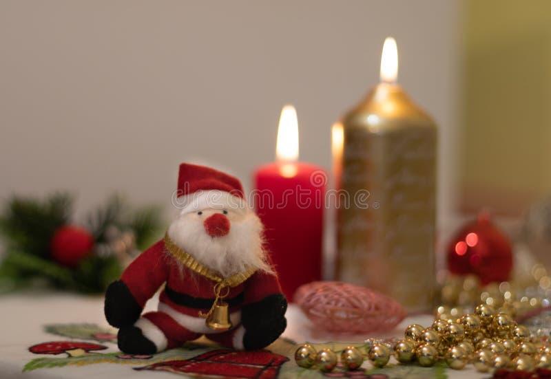 Muñeca de Santa Claus con las velas en un mantel de la Navidad fotos de archivo libres de regalías