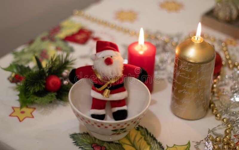 Muñeca de Santa Claus dentro de un cuenco con en un mantel de la Navidad con las velas imagen de archivo