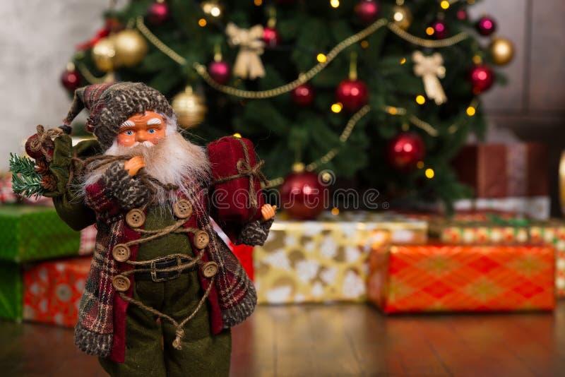 Muñeca de Santa Claus que lleva el traje tradicional y que sostiene un regalo foto de archivo