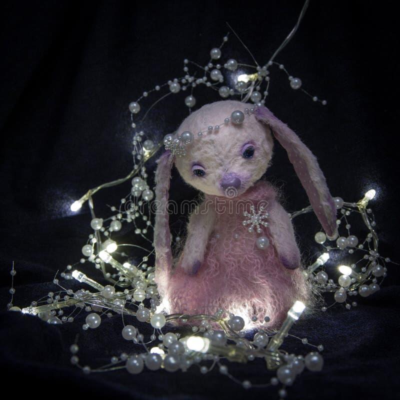 Muñeca de una pequeña muchacha de conejito triste en un vestido rosado con los ornamentos de las perlas foto de archivo libre de regalías