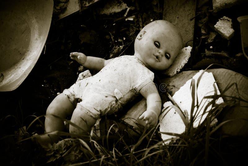 Muñeca dejada detrás en un depósito de chatarra foto de archivo