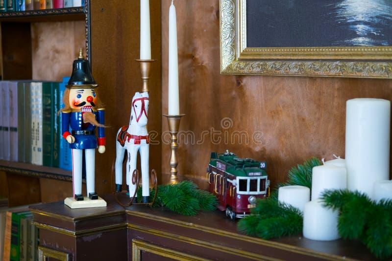 Muñeca del cascanueces en la repisa en la biblioteca El libro es el fondo fotografía de archivo libre de regalías