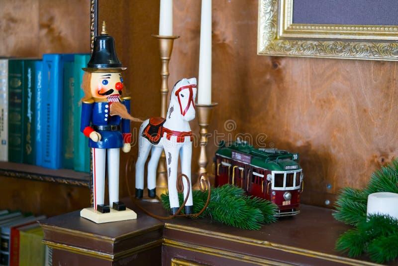 Muñeca del cascanueces en la tabla con las velas en la biblioteca El libro es el foco selectivo del fondo fotos de archivo libres de regalías