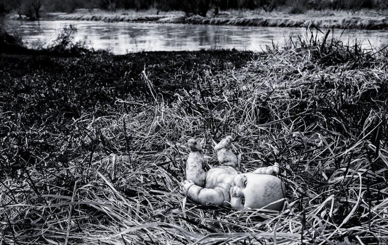 Muñeca espeluznante abandonada en hierba cerca del río imagenes de archivo