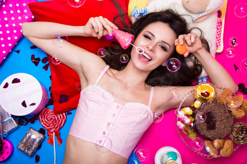 Muñeca fresca hermosa de la muchacha con las burbujas de jabón que mienten en los fondos brillantes rodeados por los dulces, los  foto de archivo libre de regalías