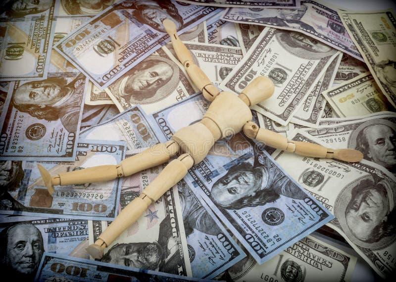 Muñeca hecha de la madera que miente en muchos billetes de banco de los americanos del dólar imágenes de archivo libres de regalías