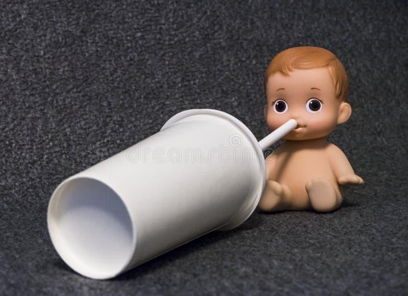 Muñeca humana del bebé que bebe con una paja de papel fotos de archivo