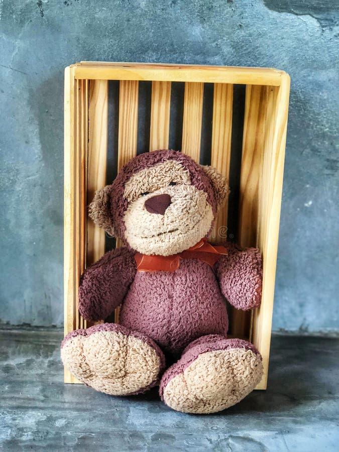 Muñeca linda de la sonrisa del mono que se sienta en la caja de madera imagenes de archivo