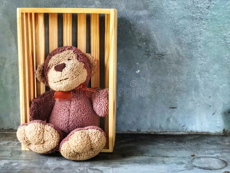 Muñeca linda de la sonrisa del mono que se sienta en la caja de madera imagen de archivo libre de regalías
