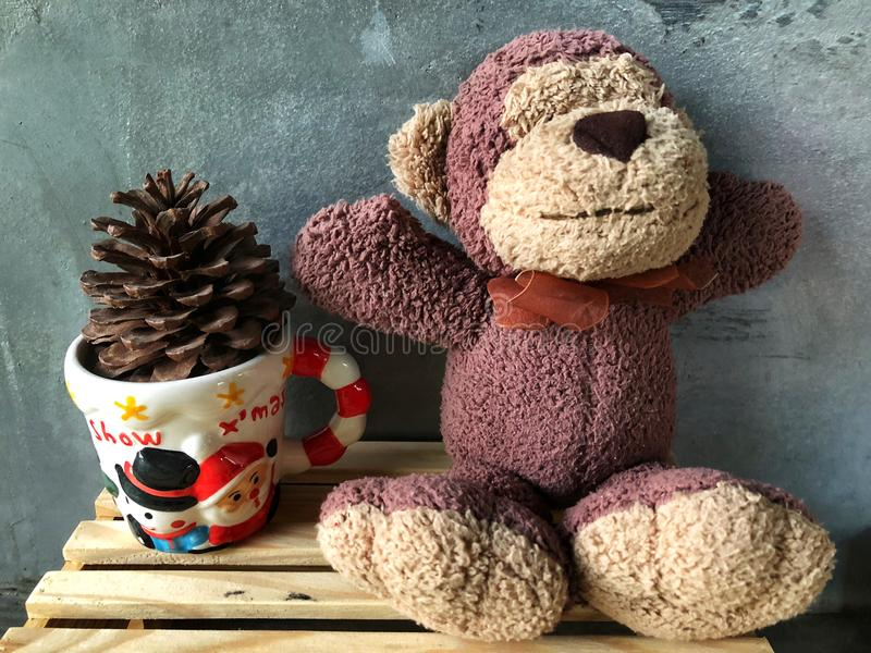 Muñeca linda de la sonrisa del mono que se sienta en la caja de madera con el fondo del cemento imagen de archivo libre de regalías
