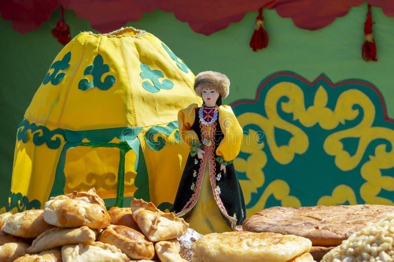 Muñeca - mujer en vestido nacional bashkir y una estatuilla del yurt al lado de los dulces nacionales bashkires, pasteles foto de archivo