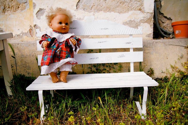 Muñeca que se coloca en banco foto de archivo
