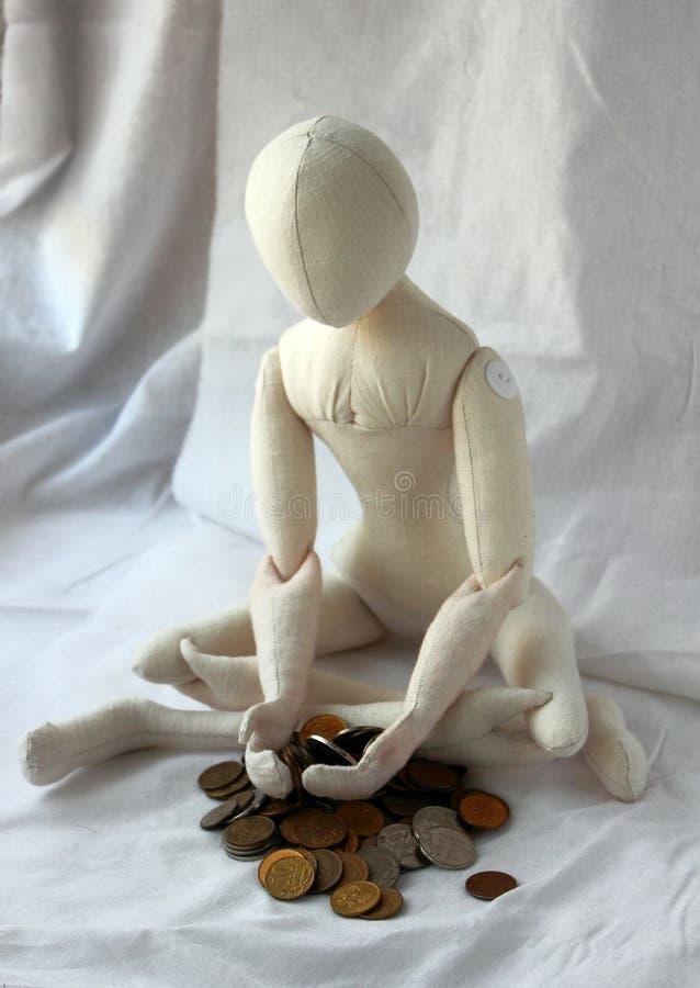 Muñeca que se sienta en la montaña que se aflige las pequeñas cosas sobre pobreza fotografía de archivo libre de regalías