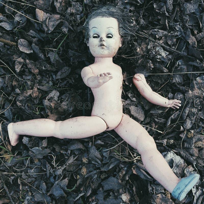 Muñeca quebrada en el de tierra - Halloween espeluznante fotografía de archivo