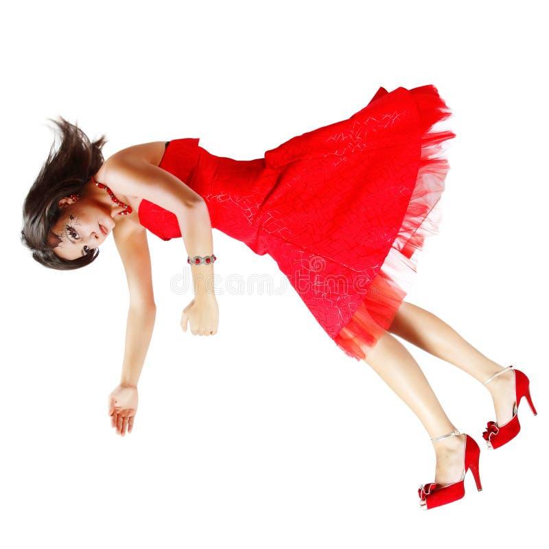 Muñeca rota mujer hermosa que cae abajo en el vestido rojo aislado encendido imagen de archivo