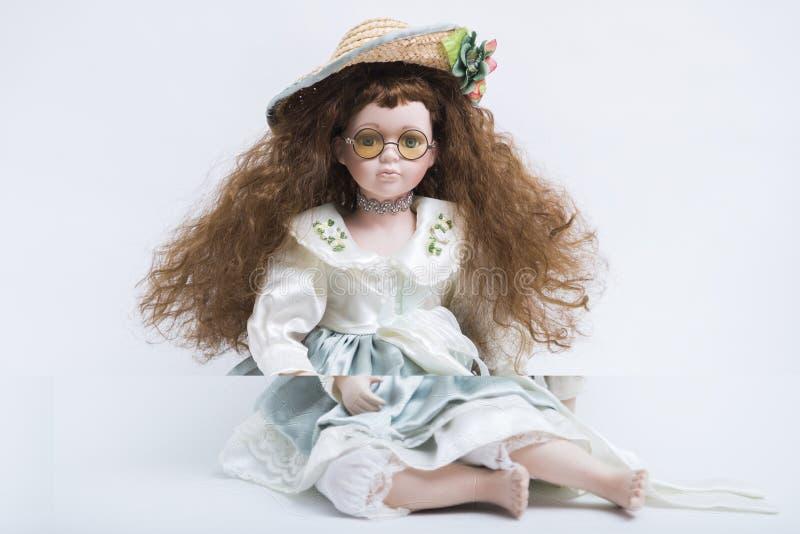 Muñeca rubia hecha a mano de la porcelana de cerámica con el sombrero de mimbre y los vidrios amarillos fotografía de archivo
