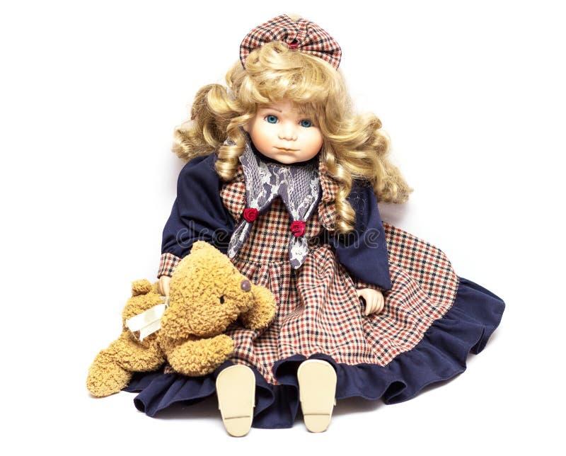 Muñeca vieja de la porcelana en el fondo blanco, muñecas de cerámica y un oso de peluche imágenes de archivo libres de regalías